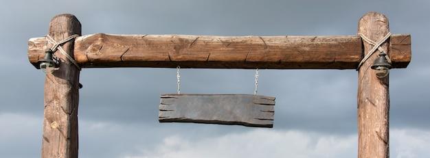 Tabuleta de madeira vazia suspensa em postes de madeira. placa de madeira em branco com copyspace pronto para sua mensagem de texto, pendurada em um poste ao lado de uma estrada rural rural, banner
