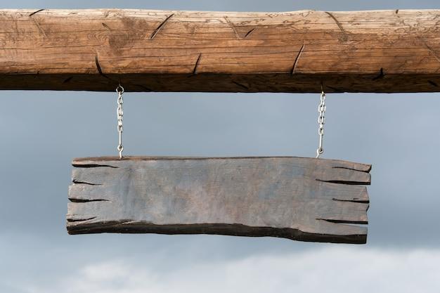 Tabuleta de madeira vazia suspensa em postes de madeira. placa de madeira em branco com copyspace pronto para sua mensagem de texto, pendurado no poste ao lado de uma estrada rural rural.