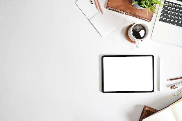 Tabuleta digital do modelo na mesa de escritório com a tabela da vista superior do espaço da cópia.