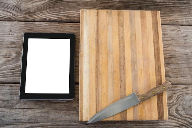 Tabuleta digital, faca e bandeja de madeira contra a superfície de madeira