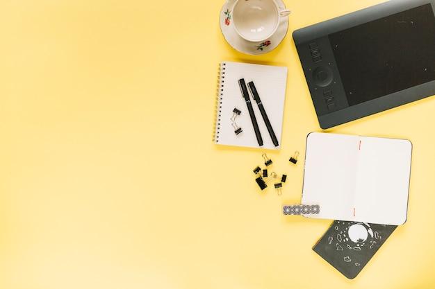 Tabuleta digital gráfica e copo vazio cerâmico com stationeries no fundo amarelo