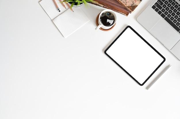 Tabuleta digital na mesa de escritório com a tabela da opinião superior do espaço da cópia.