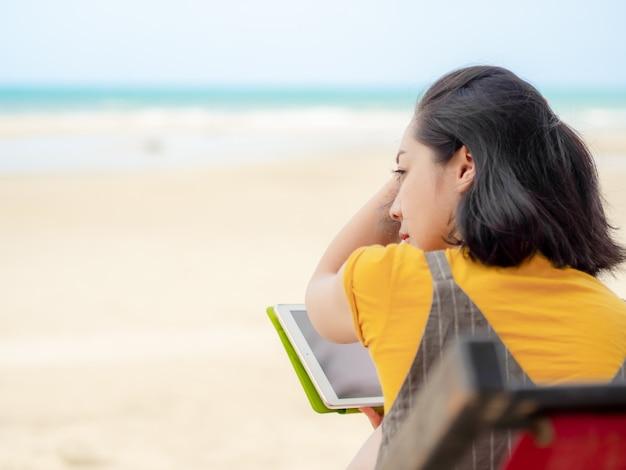 Tabuleta do uso da mulher quando relaxe na praia no verão.