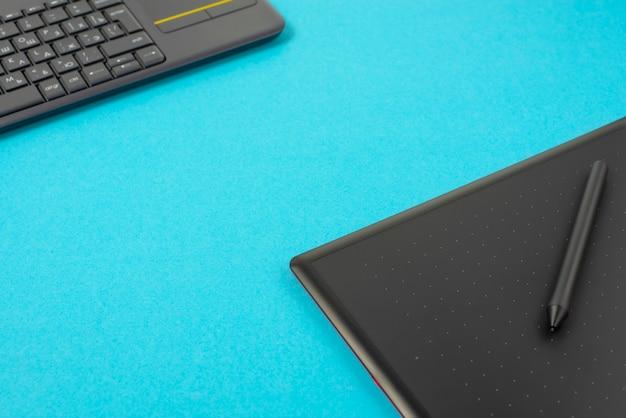 Tabuleta e teclado de gráficos em um fundo azul.