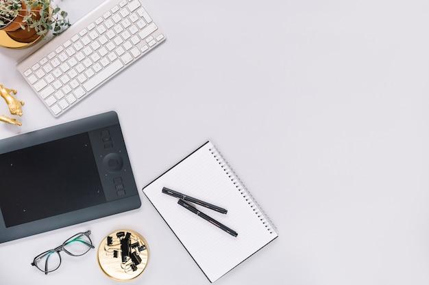 Tabuleta gráfica digital e teclado com artigos de papelaria no fundo branco