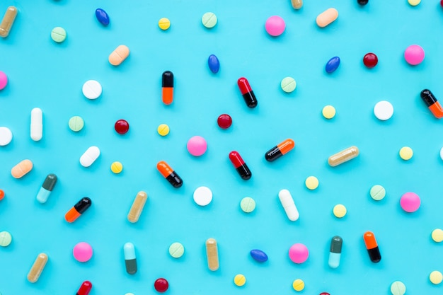 Tabuletas coloridas com cápsulas e comprimidos sobre fundo azul.