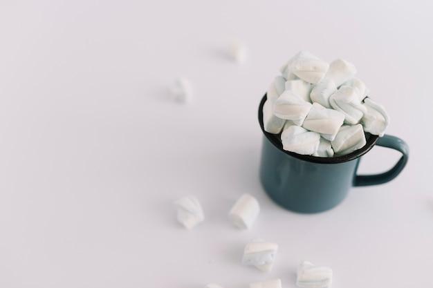 Taça azul cheia de marshmallows macios