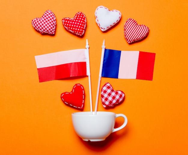 Taça branca e formas de coração com bandeiras de frança e polónia