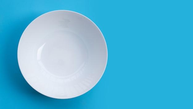 Taça branca vazia na superfície azul. vista do topo