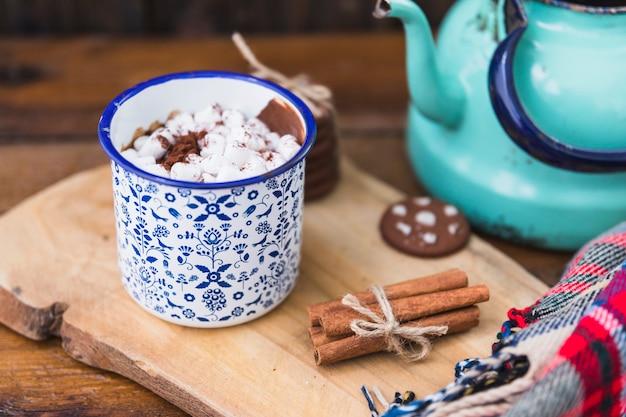 Taça com marshmallow perto de biscoitos, canela e chaleira