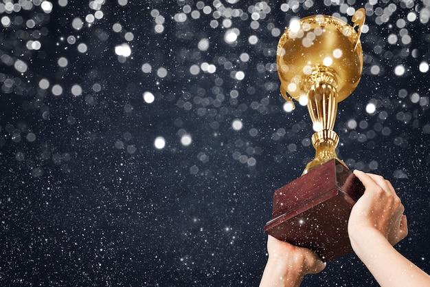 Taça da liga dos campeões nas mãos do vencedor, confetes ao fundo.