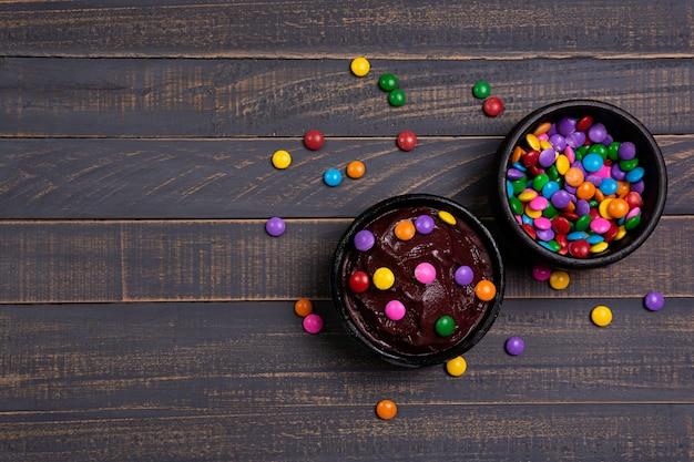 Taça de açaí com cobertura de chocolate em mesa de madeira