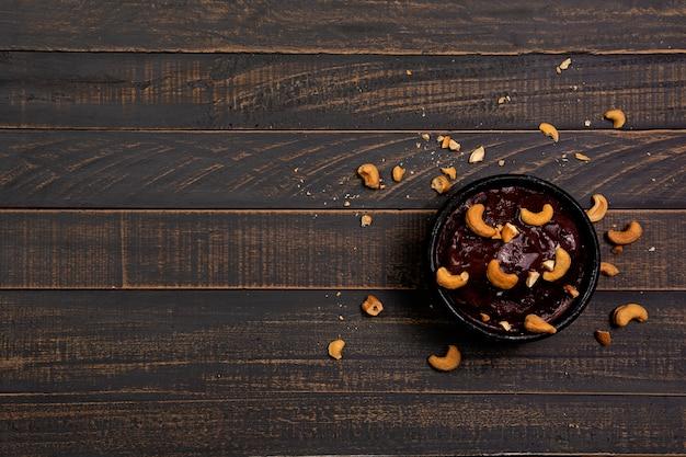Taça de açaí com nozes em madeira preta
