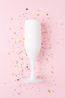 Taça de champanhe branca com confete em fundo rosa.