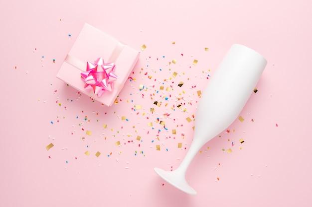Taça de champanhe branca e caixa de presente com confete em fundo rosa.