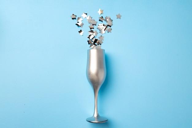 Taça de champanhe com confete plano