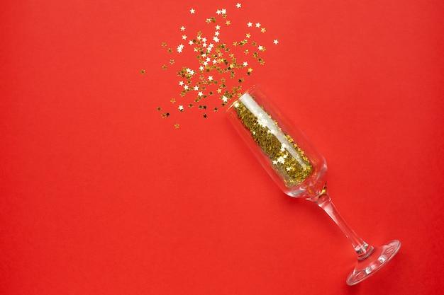 Taça de champanhe com confetes de estrelas douradas