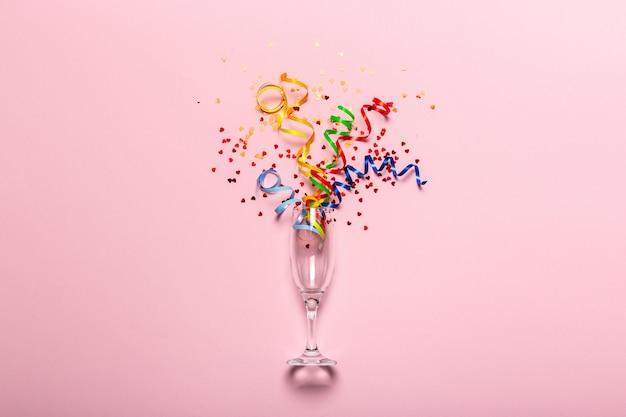 Taça de champanhe com serpentinas de festa colorida
