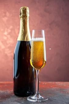 Taça de champanhe com vista frontal e garrafa na luz bebida álcool foto cor champanhe ano novo