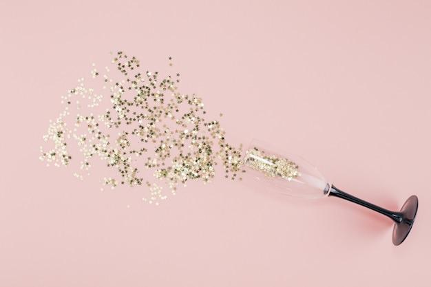 Taça de champanhe derramado confetes de estrelas douradas