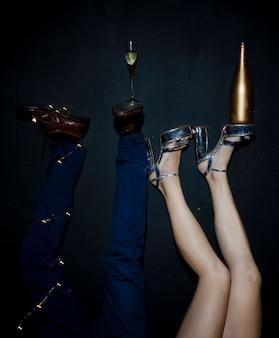 Taça de champanhe e garrafa em pés de mulher e homem