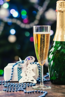 Taça de champanhe e garrafa sobre bokeh e árvore de natal