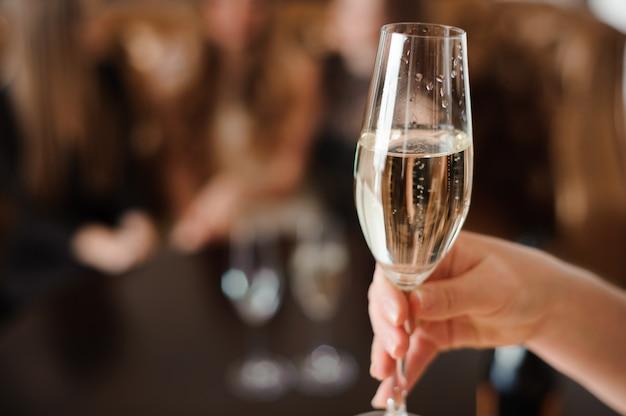 Taça de champanhe no fundo de amigos em uma festa