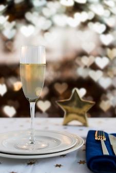 Taça de champanhe no prato com efeito bokeh em forma de coração