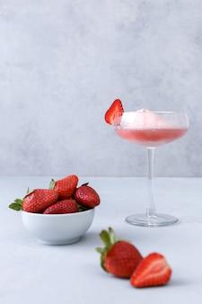 Taça de champanhe rosa com sorvete de morango em uma superfície cinza. o conceito de deliciosas bebidas. copie o espaço