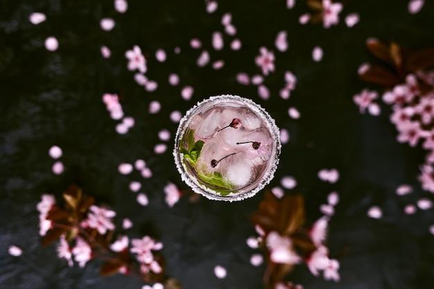 Taça de champanhe rosa rosa, cidra ou limonada com gelo e hortelã e flores de cerejeira