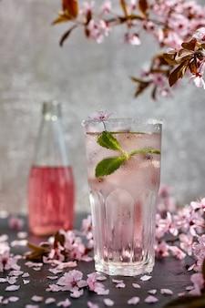 Taça de champanhe rosa rosa com gelo e hortelã. ramos de cerejeira em flor acima e flores de cerejeira espalhadas