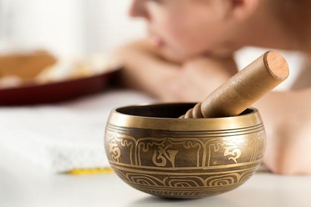 Taça de cobre do buda do nepal em salão de spa com uma jovem mulher bonita