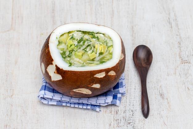 Taça de coco com sopa tradicional de okroshka de verão