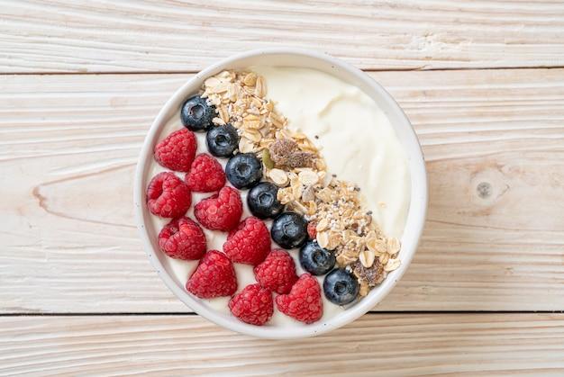 Taça de iogurte caseiro com framboesa, mirtilo e granola