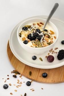 Taça de iogurte com frutas e cereais em ângulo alto