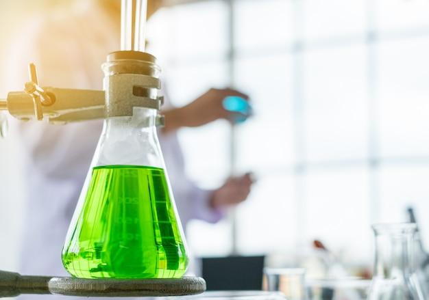 Taça de medição de vidro da cor verde com fundo do cientista em um laboratório.