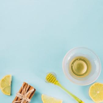 Taça de mel perto de dipper; limão e canela, sobre fundo azul