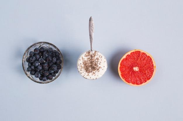 Taça de mirtilos; toranja vermelha cortada ao meio e iogurte com sementes de chia em fundo cinza