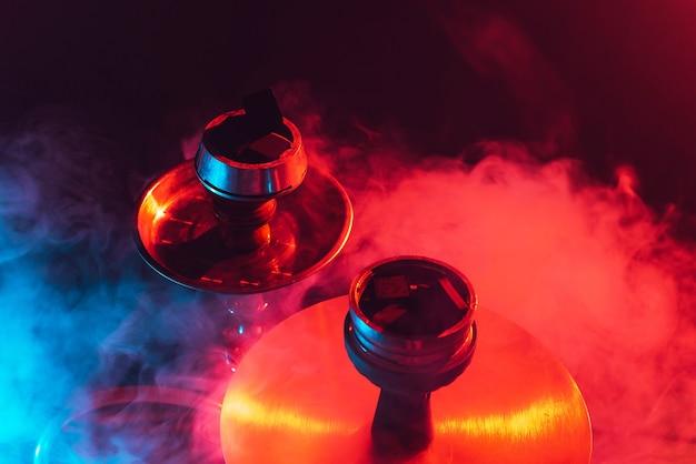Taça de narguilé, shisha e close-up de carvão em um fundo preto esfumaçado com iluminação colorida