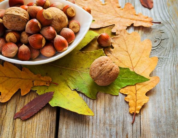 Taça de nozes e folhas de outono na velha mesa de madeira