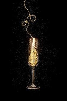Taça de ouro de champanhe em fundo preto, celebração de natal e ano novo