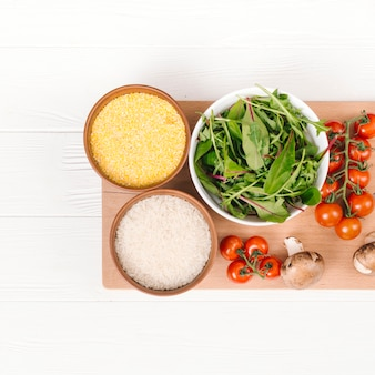 Taça de polenta; grãos de arroz; acelga; tomates de cereja e cereja na tábua sobre a prancha branca