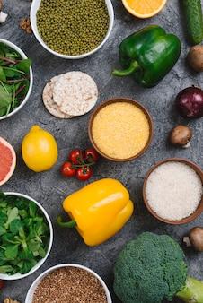 Taça de polenta; grãos de arroz; feijão mungo e vegetais folhosos no pano de fundo de concreto