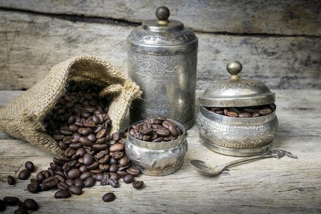 Taça de prata e grãos de café em saco de pano de saco em fundo de madeira