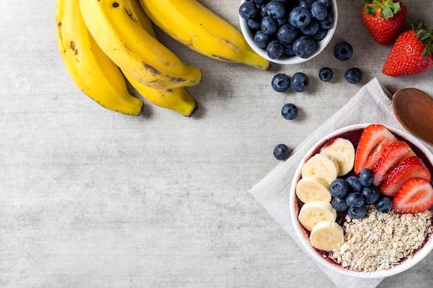Taça de sorvete brasileiro de açaí e congelados com flocos de morango, banana, mirtilo e aveia. com frutas em fundo de madeira. vista superior do menu de verão. fechar-se