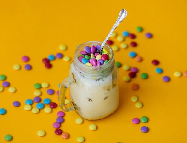 Taça de sorvete de creme com doces em drageia em amarelo