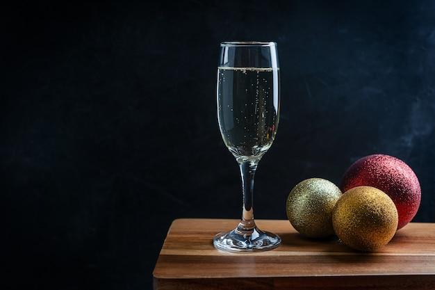 Taça de taça de champanhe gaseificada seca com bolas de natal douradas e vermelhas no balcão de madeira