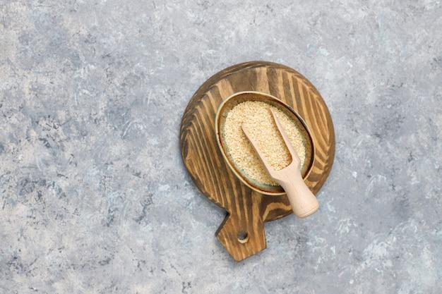 Taça de tahine com sementes de gergelim na superfície de concreto