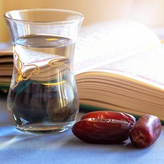 Taça de tâmaras orgânicas de água potável e livro conceito do mês sagrado do ramadã foco seletivo