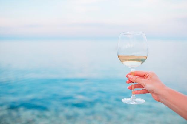 Taça de vinho branco em praia tropical